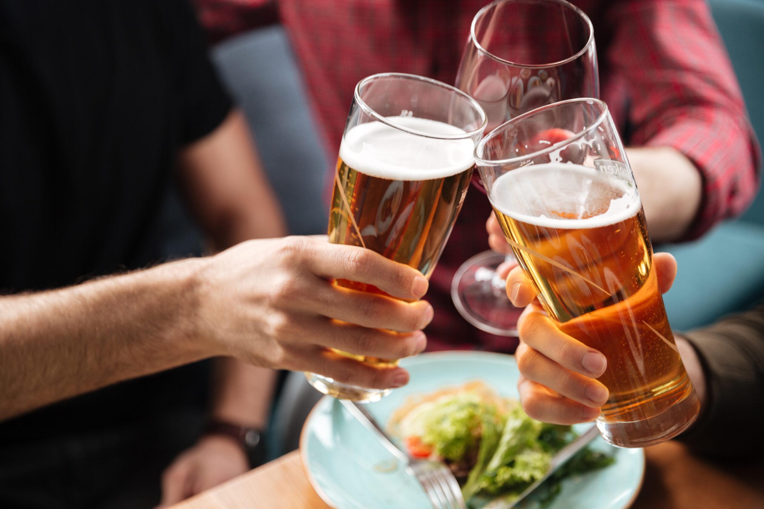 Männer stoßen mit einem Bier an